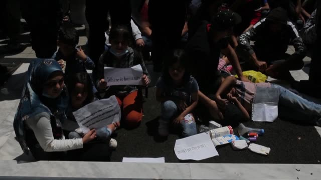 recognised refugee families protest outside the unhcr offices in athens on may 29 against the government's decision that they should leave their... - refugee camp stock videos & royalty-free footage