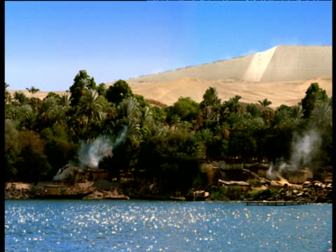 reconstruction of ancient egyptian settlement on banks of river nile pyramid in background giza - piramide struttura edile video stock e b–roll