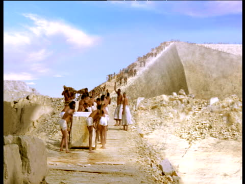 reconstruction of ancient egyptians building pyramids pushing large boulder up ramp giza - pyramid stock videos and b-roll footage