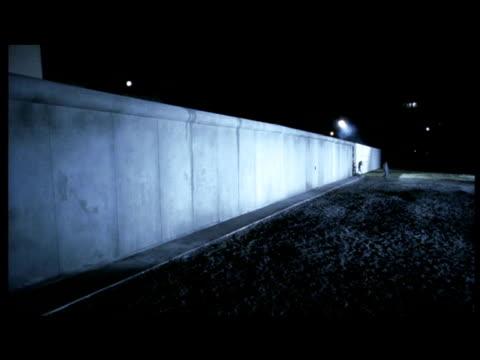 reconstruction of people escaping through opening in berlin wall. - gefängnisausbruch stock-videos und b-roll-filmmaterial