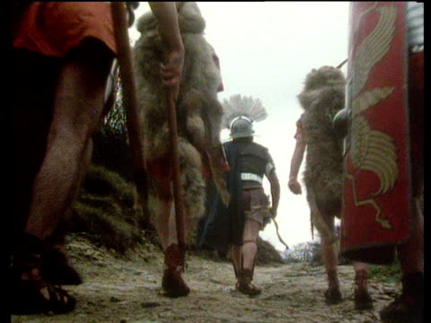 vídeos de stock, filmes e b-roll de reconstruction of roman soldiers in battle dress marching away from camera - roman soldier