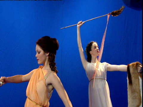 reconstruction of two roman women dancing in front of a blue screen. - toga stock videos and b-roll footage