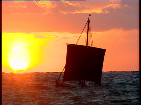 reconstruction of viking ship sailing against sunset on north sea - viking stock videos and b-roll footage