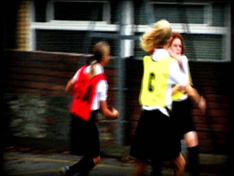 reconstruction: school girls wearing bibs play netball in playground goal attack misses net - girls videos stock videos & royalty-free footage