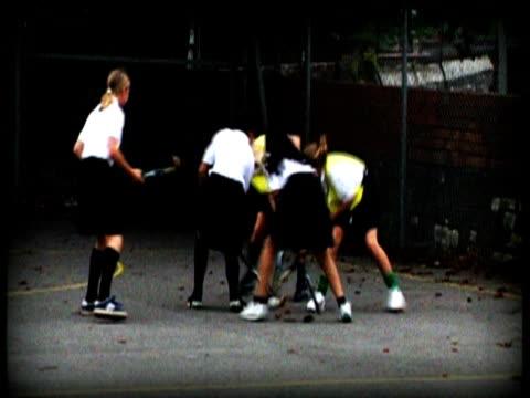 reconstruction: school girls wearing training bibs play hockey in playground - field hockey stock videos and b-roll footage
