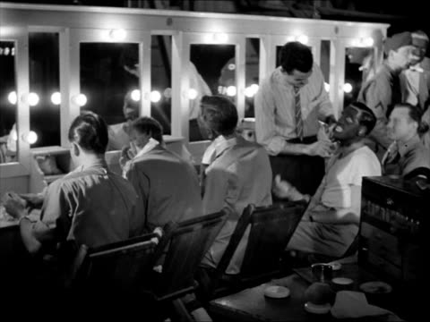 Record album cover 'This is the Army' WS Soldiers at makeup mirrors makeup artist applying blackface Director Michael Curtiz producer Hal Wallis amp...