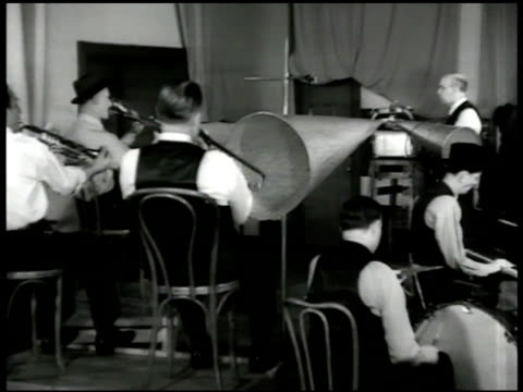 Record cover 'Dixieland Jazz Band' CU Sign 'Recording Room B Quiet Please' INT VS Band members playing jazz trombone bass drum brass VS CU Recording...