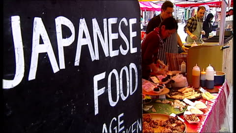 record number of workers in low-paid jobs; ext **gardiner interview overlaid sot** sign 'japanese food' at food stall people along at market food on... - japanese food stock videos & royalty-free footage