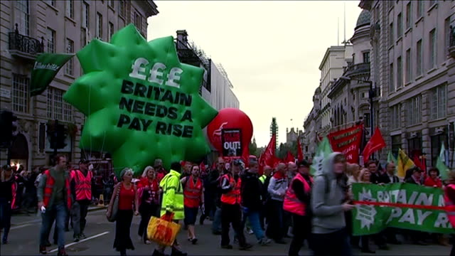 record number of workers in low-paid jobs; tx ext people along on tuc demonstration including inflatable green sign 'britain needs a payrise' various... - 労働組合会議点の映像素材/bロール