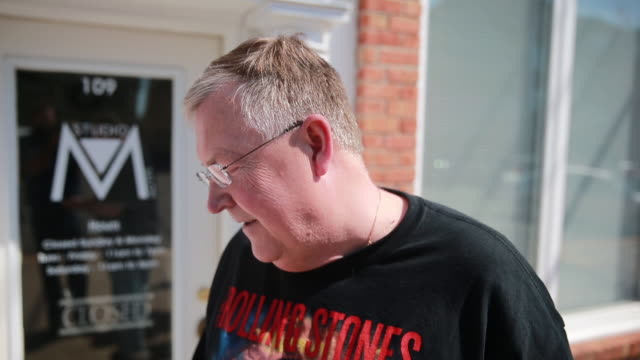 stockvideo's en b-roll-footage met record shopper reads the list of records he's looking for outside landlocked records during record store day, april 16, 2016 in bloomington, indiana... - audio available