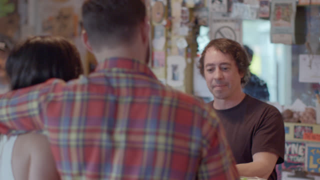 Record store owner points to friend and rings up customer at checkout counter