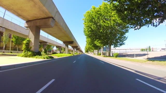 Recording Barcelona city streets with beautiful concrete urban infrastructures from car point of view with motion in a sunny day and low traffic.