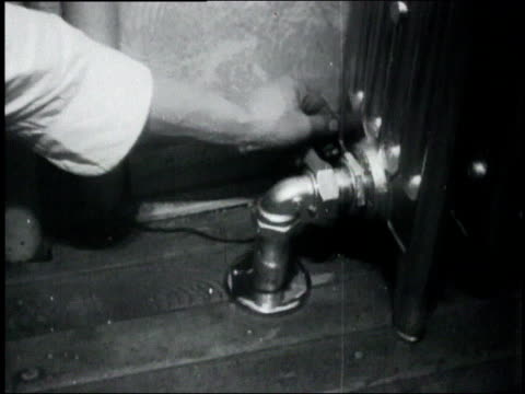 cu recording device being pulled out from behind a radiator / united states - 1932 stock-videos und b-roll-filmmaterial