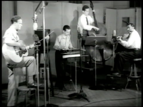 vídeos de stock e filmes b-roll de recording light 'silence' int vs singer eddy arnold w/ guitar amp band playing in recording studio singing vs arnold singing 'echo of your footsteps'... - 1947