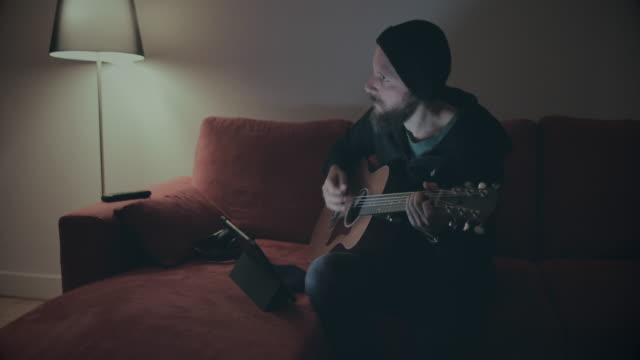 vídeos de stock e filmes b-roll de recording studio at home: guitar and tablet - homem e máquina