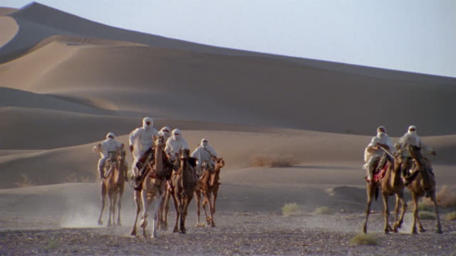 SLO MO, WS, CU, TD, Re-creation, Africa, Tuareg tribesmen charging through desert