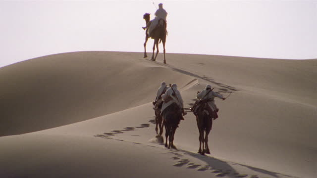 vídeos de stock e filmes b-roll de ws, re-creation, africa, tuareg tribesmen riding camels in desert, rear view - soldado exército
