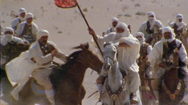 slo mo, cu, td, re-creation, africa, tuareg troops charging through desert - arabic script stock-videos und b-roll-filmmaterial