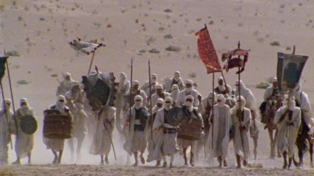 vídeos de stock, filmes e b-roll de slo mo, ms, re-creation, africa, tuareg troops walking through desert - montar um animal