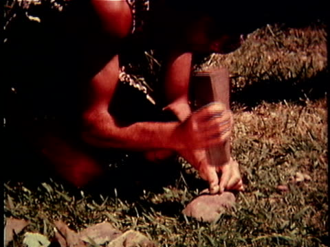 re-creation ms caveman pounding on nut with rock to open nutshell / usa - nutshell stock videos & royalty-free footage