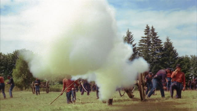 vídeos de stock, filmes e b-roll de recreation low angle wide shot union soldiers firing cannon during civil war battle - exército da união