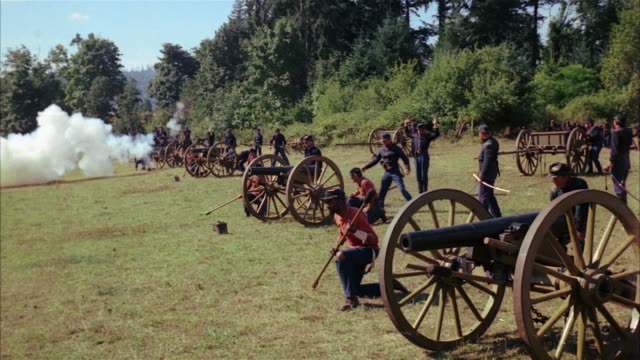 vídeos de stock, filmes e b-roll de recreation low angle wide shot union soldiers firing cannons during civil war battle - exército da união