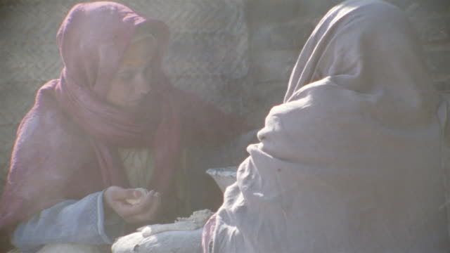 cu, re-creation, middle east, two women baking flatbread on medieval village street - reenactment stock videos & royalty-free footage