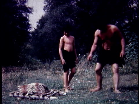 re-creation montage ws caveman dragging board with dead animal on it / ms boy helping caveman roll invention across field / usa - barefoot stock videos & royalty-free footage