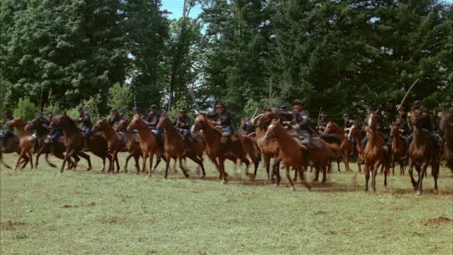 recreation wide shot union soldiers on horseback charging during civil war battle - bürgerkrieg stock-videos und b-roll-filmmaterial