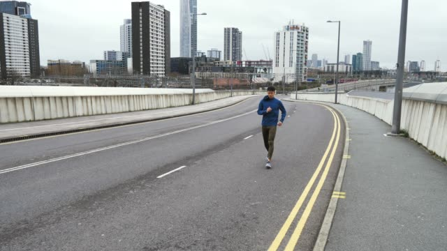 recreational jogger in orange clothing exercising on cloudy day. - london marathon stock videos & royalty-free footage