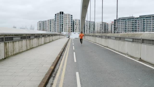 FreizeitspJogger in orangefarbener Kleidung trainieren am bewölkten Tag.