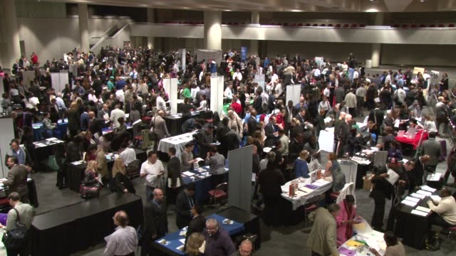 recruiters meeting with job seekers to discuss employment opportunities. interior the job fair main floor. putting america back to work! job fair at... - 就職フェア点の映像素材/bロール