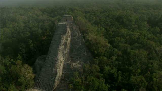 a rectangular doorway tops the nohoch mul pyramid in the ancient mayan city of coba. available in hd. - civiltà maya video stock e b–roll
