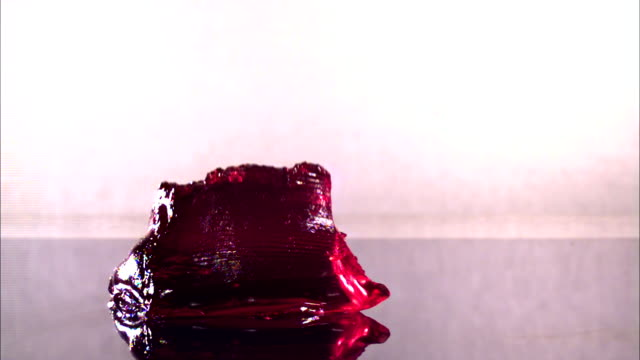 a rectangular piece of red jello falls onto a reflective surface. - gelatin stock videos & royalty-free footage