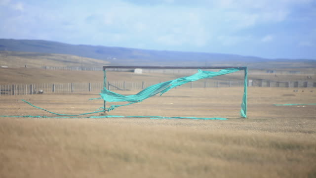 ms rectangular structure with green fabric attached and blowing in wind in yellow vast plain - 焦点点の映像素材/bロール
