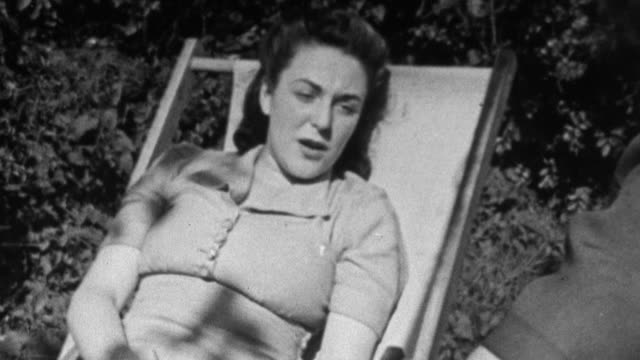 vídeos de stock e filmes b-roll de 1943 montage recuperating tuberculin patients lounging outside on sanatorium grounds on warm day and doctor conversing with patient / united kingdom - tuberculose