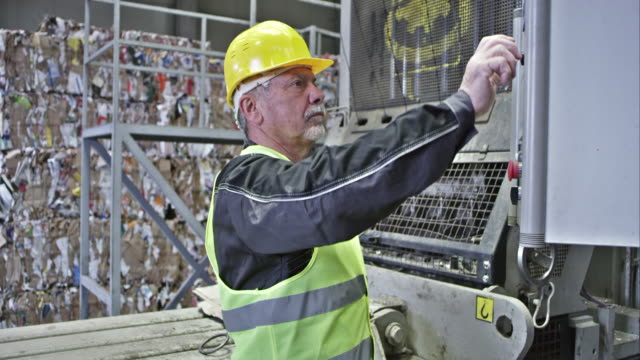 tu återvinning facility arbetare verksamma av pressning pressmaskin - maskineri bildbanksvideor och videomaterial från bakom kulisserna