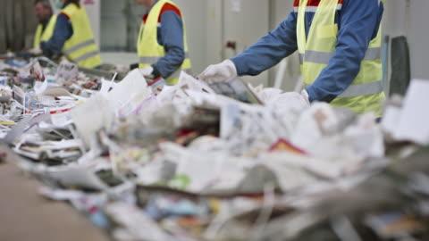 stockvideo's en b-roll-footage met recycling facility werknemers scheiden afval met de hand op transportband - recycling