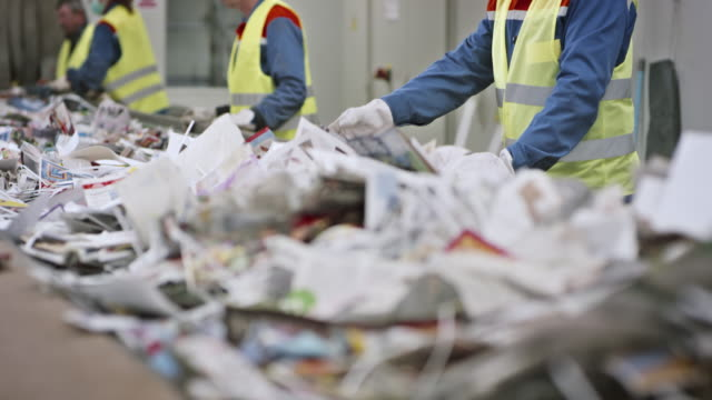 Recycling facility workers separating waste by hand on conveyor belt