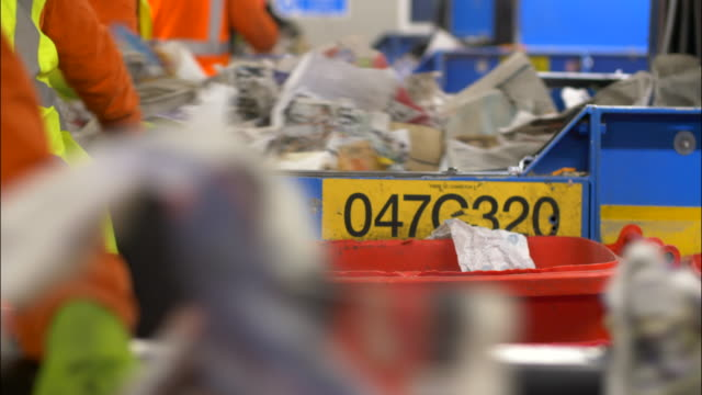 recycling plant workers sort through waste plastics refuse and garbage on conveyor belts - waste management stock videos & royalty-free footage