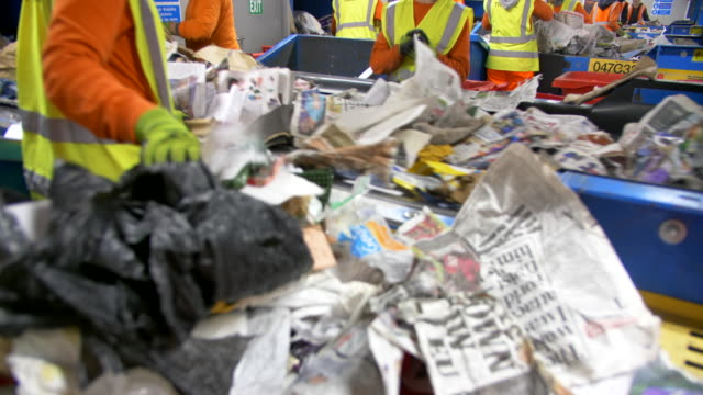 recycling plant workers sort waste refuse rubbish on conveyor belts, plastics paper and recycled waste - waste management stock videos & royalty-free footage