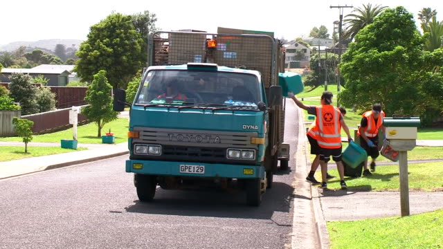 Recycling truck moving along residential street with workers emptying waste from bins into back of truck