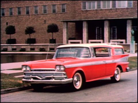 WS red 1958 AMC Ambassador Custom fourdoor hard top station wagon drives up to camera / XWS Ambassador slowly pulls up and stops at curb next to...