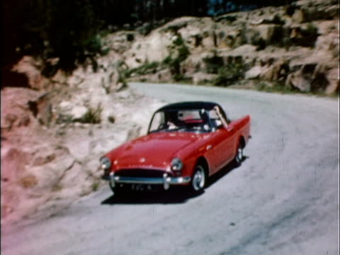 1959 ws pan red 1959 sunbeam alpine driving along winding road / united kingdom - classic car stock videos and b-roll footage