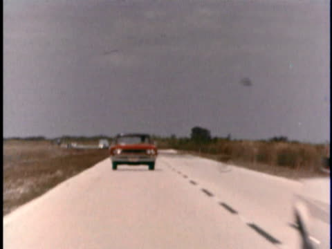vidéos et rushes de montage ws red 1967 amc rambler rebel diving on two lane road as car moves into its lane to pas another car/ rambler driving off road to avoid oncoming car before turning back onto road/ usa - 1967