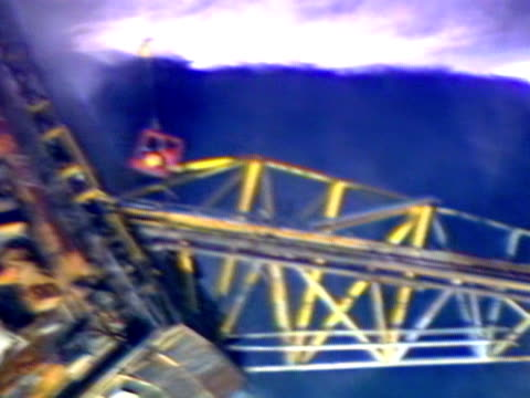 red adair and two engineers are lowered by helicopter to inspect the wreckage of the piper alpha oil rig. - alpha cell stock videos & royalty-free footage