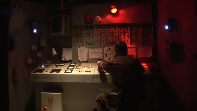 vídeos de stock e filmes b-roll de a red alarm goes off at a control booth that explodes in front of the technician. - sala de casa