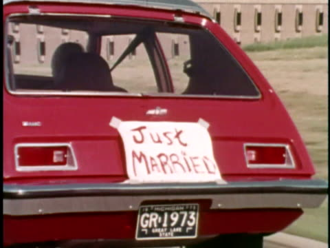 vídeos de stock e filmes b-roll de cu zo 1973 red amc gremlin driving on road with just married sign on back/ usa - casal casado