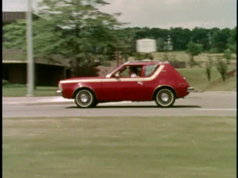 MONTAGE WS Red AMC Gremlin on road/ MS Man's foot pressing on gas pedal/ MS Gremlin/ USA