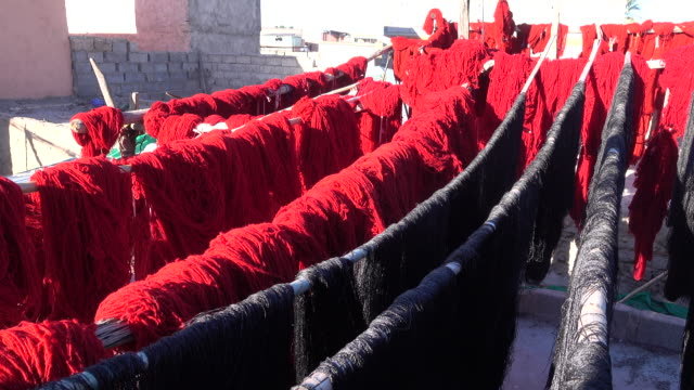 red and black dyed wool dries in the sun - dye stock videos & royalty-free footage